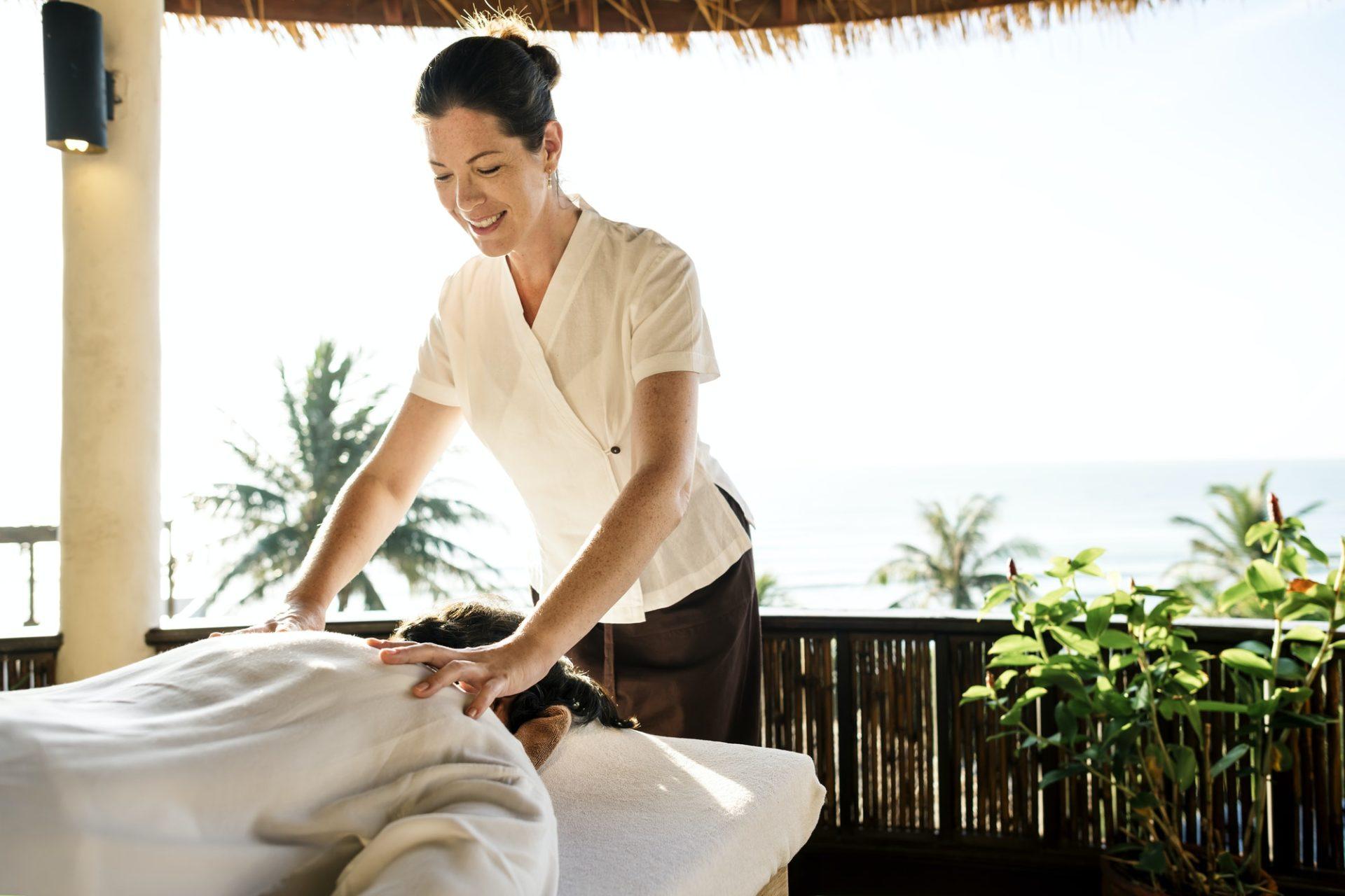 Female massage therapist giving a massage at a spa