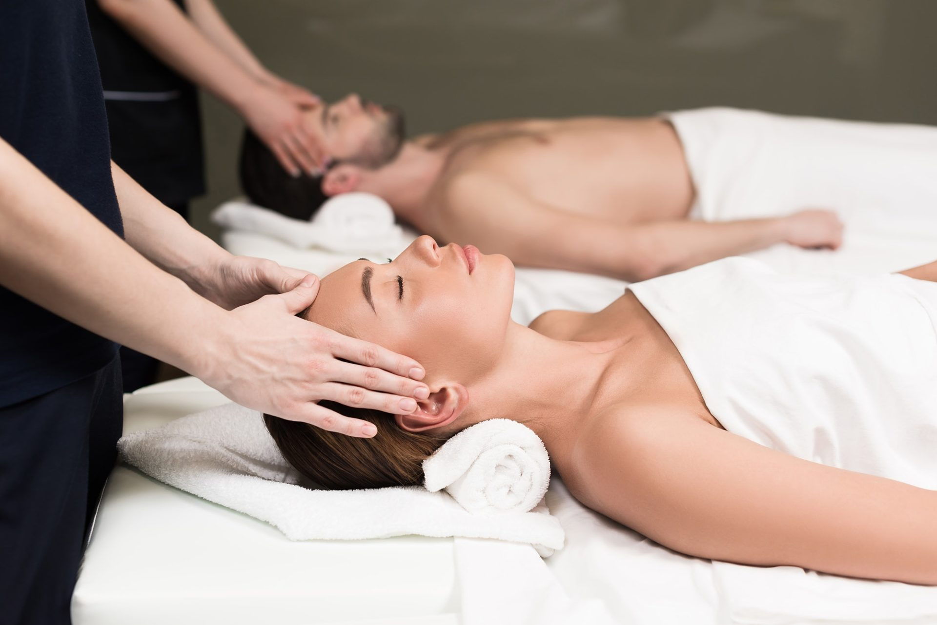 side view of young couple having massage in spa salon