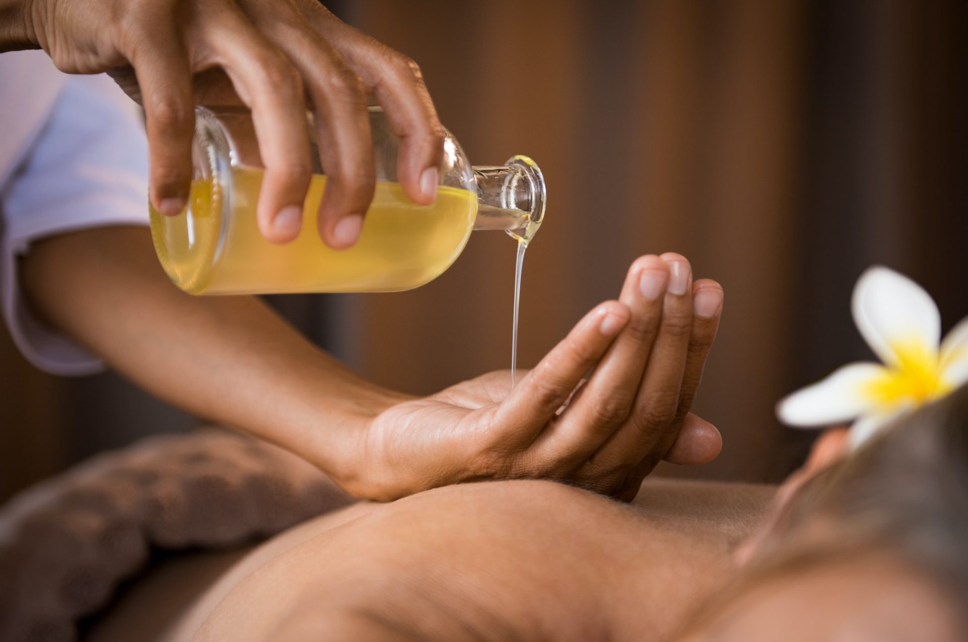 Therapist pouring massage oil at spa